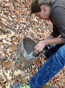 "Here's Jamie, mixing the dry into the wet slurry we couldn't get out. The mouth of the footings was just big enough to get our 1 gallon bucket through. Once through the opening, you could tip it on the side to try to fill up with slurry, then drag it back up. That stick she's using is about 2.5"" thick, and 5 feet long. My arms weren't long enough to get all the mess out of the bottom, so we mixed in place. This was the best of the lot: still enough sidewall integrity so we didn't have to dig anew. Everything else was a re-do."