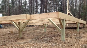 """After a final check for square, I went back under and placed supporting members for our posts. These will keep the whole thing from wobbling. Again, 6"""" timberlocks are binding these to the posts and to the framing. Jamie and I agree that these are aesthetically pleasing, too."""